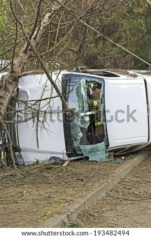 ROSEBURG, OR, USA - APRIL 25, 2014: Fire fighters and police at a single vehicle accident that rolled and hit a power pole and trees resulting in minor injuries to the driver. - stock photo