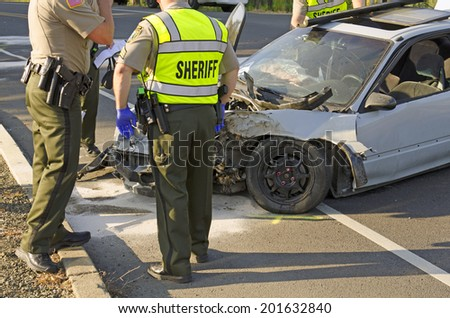 ROSEBURG, OR, USA - MAY 30, 2014: Police and fire fighters survey the scene of a single vehicle accident due to excessive speed sends the driver to the hospital in Roseburg, OR, on May 30, 2014