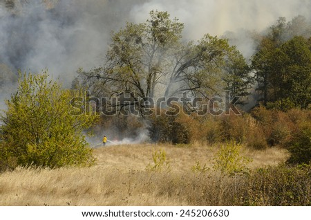 Roseburg, OR, USA - September 12, 2014: Fire fighters work with aviation helicopters to suppress a natural cover brush and grass fire in southern Oregon - stock photo