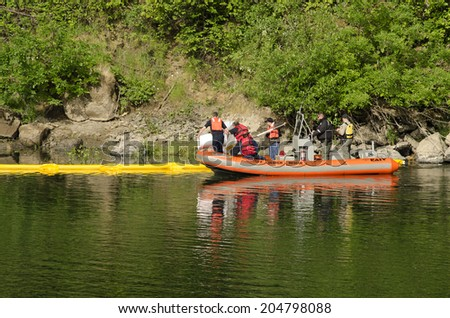 ROSEBURG, USA, USA - JUNE 02, 2014: Roseburg Hazardous materials team use a Douglas County Sheriff boat to deploy a floating oil containment boom on the Umpqua River following an vehicle accident