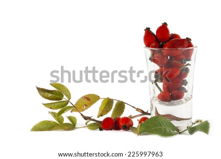 Rosehip berries in a glass isolated on white background