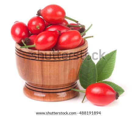 rosehip berries in a wooden bowl isolated on white background