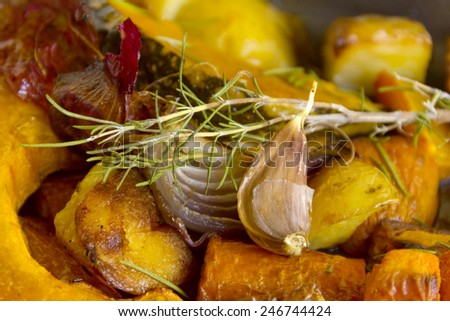 Rosemary and garlic on baked rustic vegetables straight from the oven. - stock photo