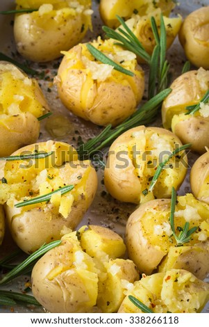 Rosemary baked potatoes with garlic and sea salt on baking tray, close up. Delicious side dish for Christmas table - stock photo