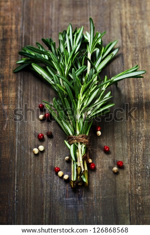Rosemary bound and pepper on a wooden board - stock photo