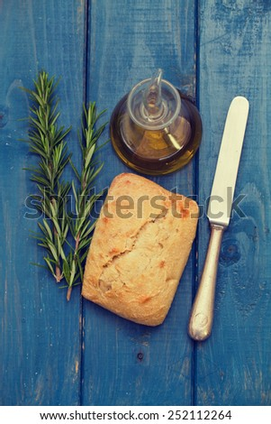 rosemary, bread and oil on blue background - stock photo