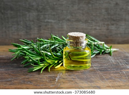 Rosemary essential oil in a glass bottle - stock photo
