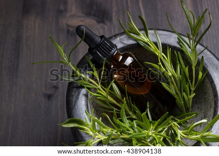 Rosemary essential oil in a mortar, aromatherapy on dark wooden background - stock photo