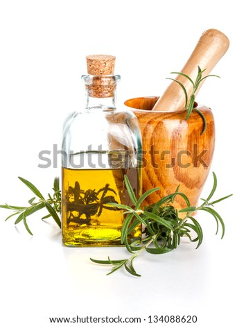 Rosemary oil bottle and mortar with fresh rosemary - stock photo
