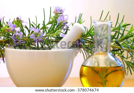 Rosemary oil with mortar and pestle with branch full of flowers - stock photo