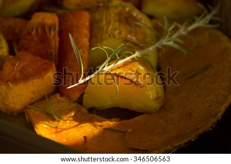 Rosemary on baked rustic potato, pumpkin and vegetables straight from the oven.