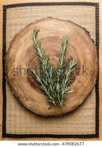 rosemary on circular wooden chopping board