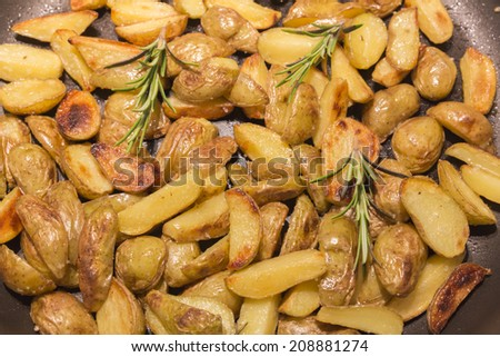 Rosemary potatoes in a frying pan - stock photo