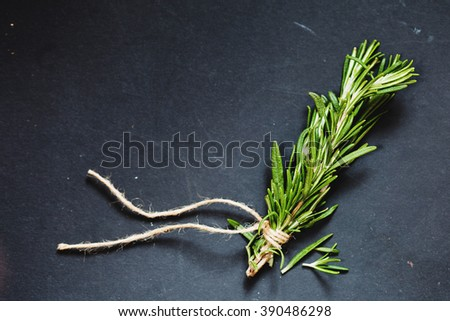 Rosemary sprigs tied with string on a grey background - stock photo