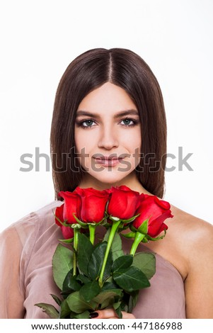 Roses and beauty. Beautiful young woman in pretty dress holding bouquet of flowers while standing against white background - stock photo