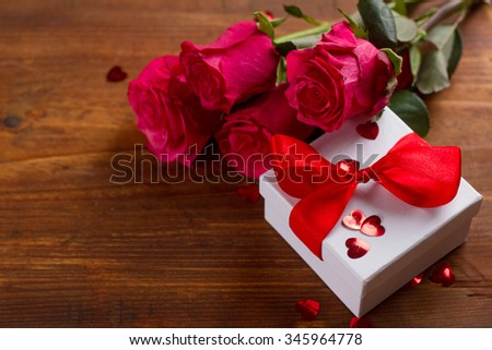Roses and gift on wooden board, Valentines Day background, selective focus - stock photo