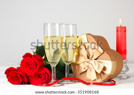 roses and glasses of champagne with gift and candle on white wooden table - stock photo