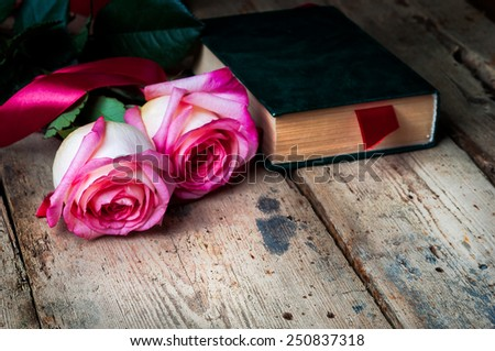 Roses and green old book with a bookmark on wooden background. - stock photo