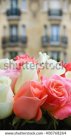 Roses and typical Parisian building at background. Selective focus on the rose in the right corner. - stock photo