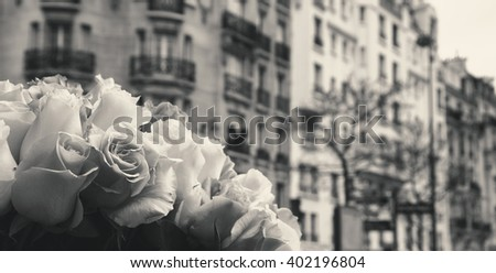 Roses and typical Parisian street at background. Aged photo. Black and white. - stock photo
