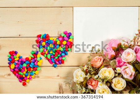 Roses flowers and empty tag for your text on wooden background Pastel color tone - stock photo