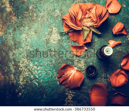 Roses flowers with petal and essential oil on rustic vintage background, top view , place for text. Aromatherapy and cosmetic concept - stock photo