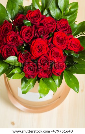 Roses in a box on wooden background