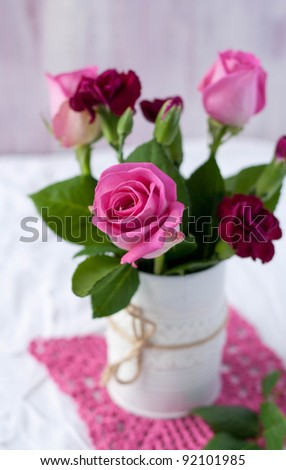 Roses in a white tin can with twine jute - stock photo