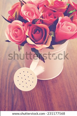 Roses in watering can for decoration with retro filter effect - stock photo