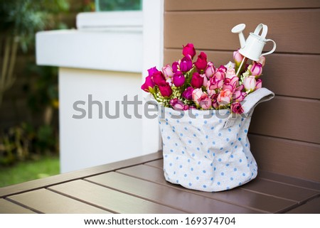 Roses with a small watering pot in fabric vase - stock photo