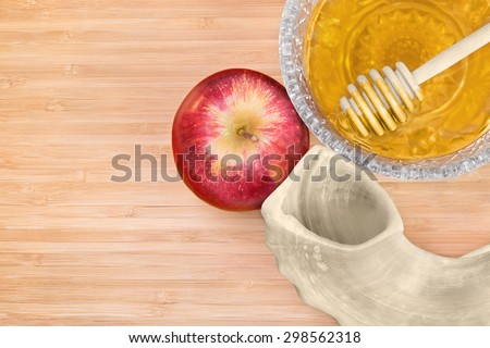 Rosh Hashana shofar,whole red apple,glass honey bowl,dipper stick,wood grain background,top down view.Soft drop shadow,natural light and dark wood texture.Sweet food for the Jewish New Year holiday.  - stock photo