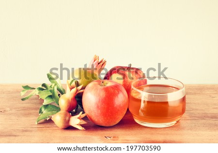 rosh hashanah concept - apple honey and pomegranate over wooden table. filtered image.