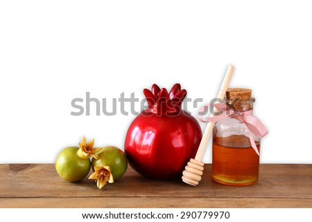 rosh hashanah (jewesh holiday) concept - honey and pomegranate over wooden table and isolated on white background. traditional holiday symbols.