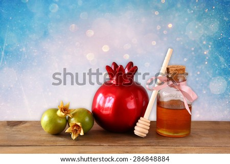 rosh hashanah (jewesh holiday) concept - honey and pomegranate over wooden table. traditional holiday symbols. - stock photo