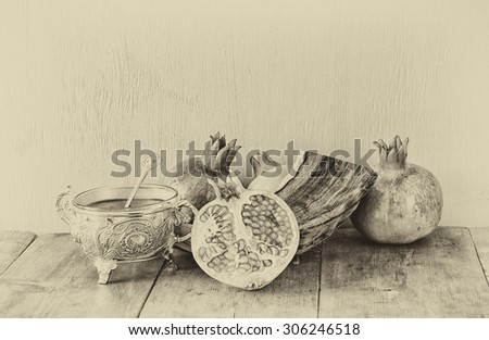 rosh hashanah (jewesh holiday) concept - shofar, honey, apple and pomegranate over wooden table. traditional holiday symbols.  black and white old style photo - stock photo