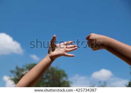 roshambo sign with a bright sky background, Rock paper scissors