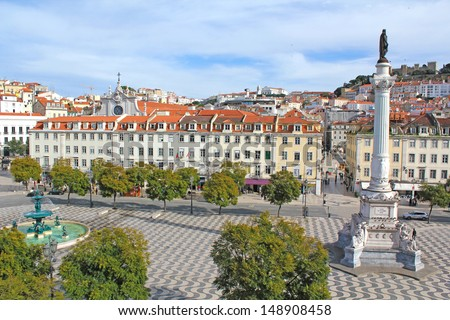 Rossio square in the central Lisbon with a monument of the king Pedro IV and a view on the castle San Giorgio - stock photo