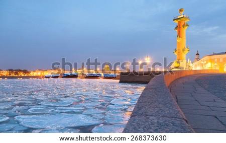 Rostral column on Vasilevsky Island and broken ice on the Neva in St. Petersburg, Russia - stock photo