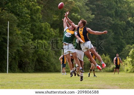 ROSWELL, GA - MAY 17:  Players jump and compete for the ball in an amateur club game of Australian Rules Football in a Roswell city park, on May 17, 2014 in Roswell, GA.  - stock photo