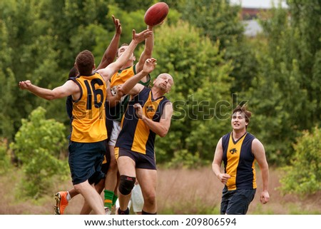 ROSWELL, GA - MAY 17:  Several players jump to catch ball in an amateur club game of Australian Rules Football in a Roswell city park, on May 17, 2014 in Roswell, GA.  - stock photo