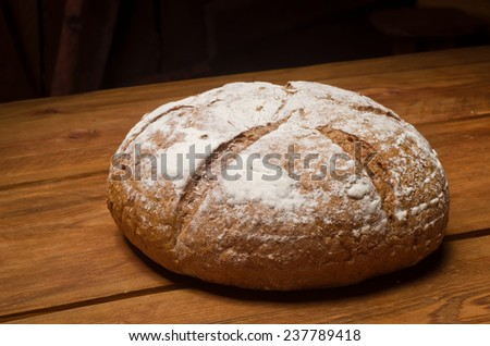 Rosy loaf of bread lying on a wooden table - stock photo