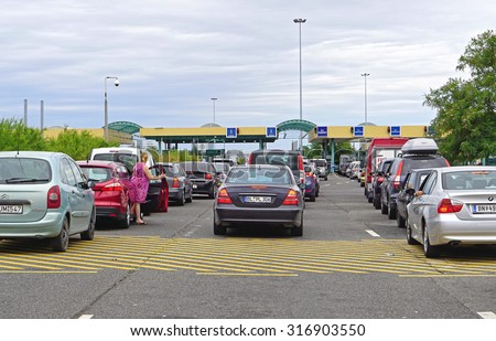 ROSZKE, HUNGARY - JULY 09, 2015: Long lines at border crossing in Roszke, Hungary. Traffic jam at customs checkpoint between Serbia and Hungary. - stock photo