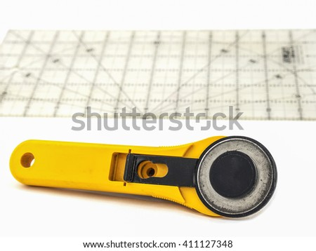 Rotary for embroidery work with plastic ruler plate over white background