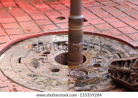Rotary table while drilling oil well and pipe being rotated and a slip on the floor - stock photo