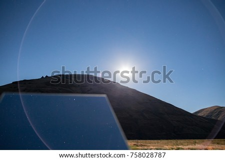 Rotating creative mirror in the desert at night blue moonlit sky