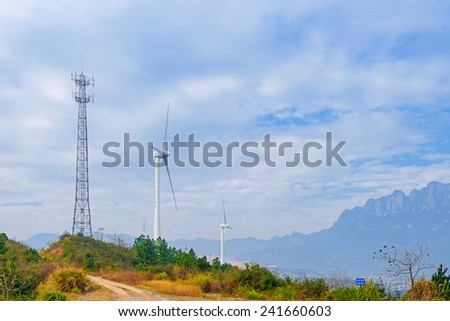 rotating wind turbine in front of cloudy sky