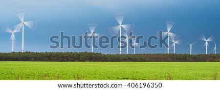 Rotating wind turbines in nature after the thunderstorm - stock photo