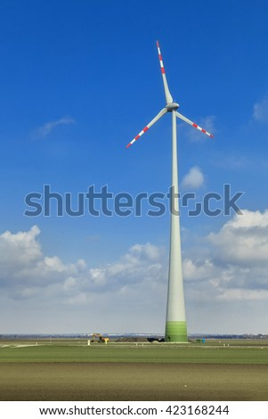 Rotating windmill blades in cloudy blue sky
