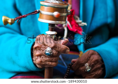 rotation buddhist prayer wheel at old woman's hand, Nepal