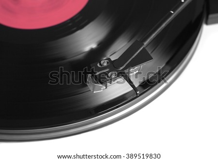Rotation vinyl record with red label on turntable player in silver case. Horizontal photo top view closeup
